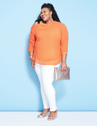 A woman wearing a plus size outfit including an orange blouse and white plus size denim pants