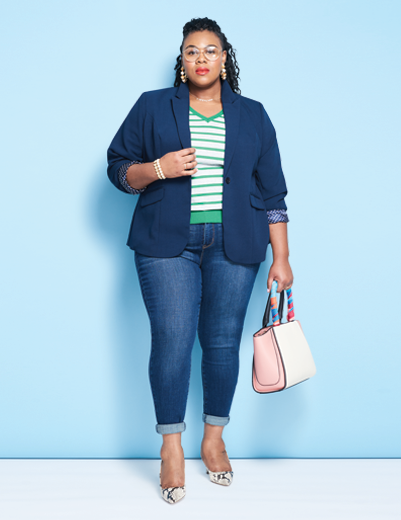 A woman wearing an outfit including plus size denim jeans and a sharp blazer