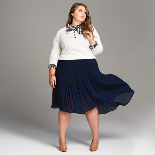 Dia Stylist Megan in a pleated navy skirt, and striped button down layered under a sweater.