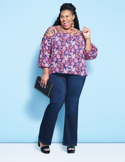 A woman wearing a plus size outfit including plus size denim bootleg jeans, a bold patterned top, and holding a black purse