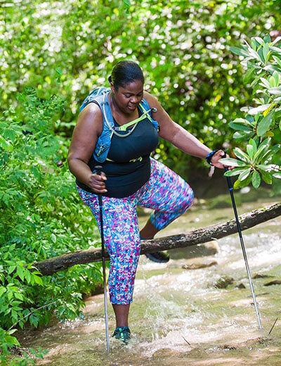 plus size fitness influencer mirna valerio of @themirnavator hikes through a river