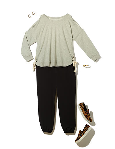 One of many casual outfits available at Dia&Co, this plus size outfit features a lace-up sweatshirt, black plus size joggers, and sneakers.