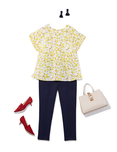 This preppy style outfit features navy trousers, a lemon-printed top, red heels and an ivory purse.