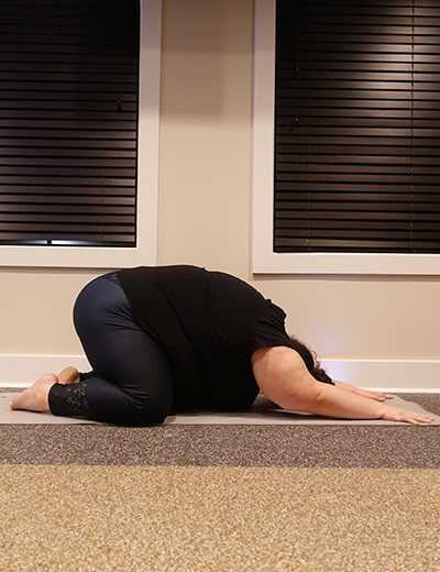plus size woman doing yoga childs pose