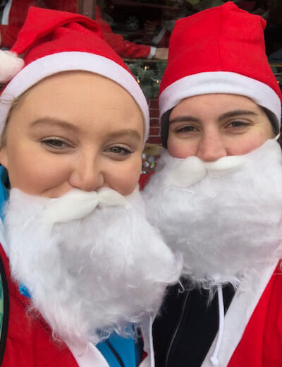 Dia Stylist Ashby and Sarah wear Santa suits in preparation of the Santa Run.