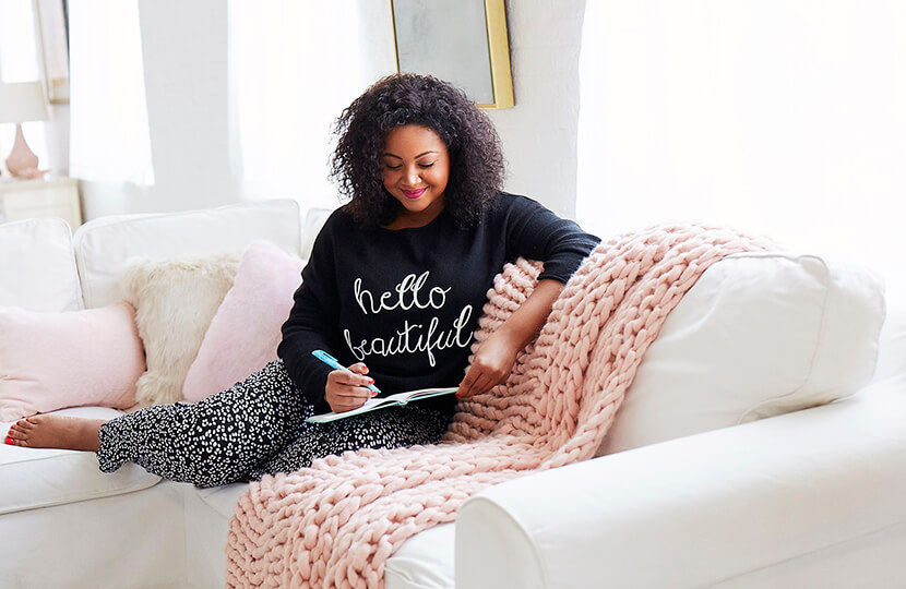 woman writing in journal in plus size athleisure and sitting on couch