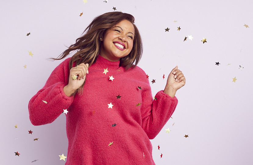 Model in fuchsia sweater, dancing, smiling, and surrounded by confetti.