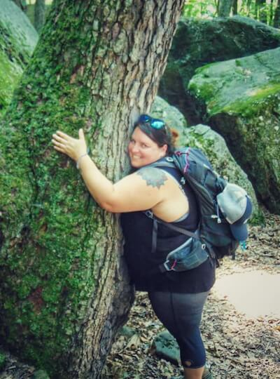 Andrea DiMaio on a hike, hugging a tree.