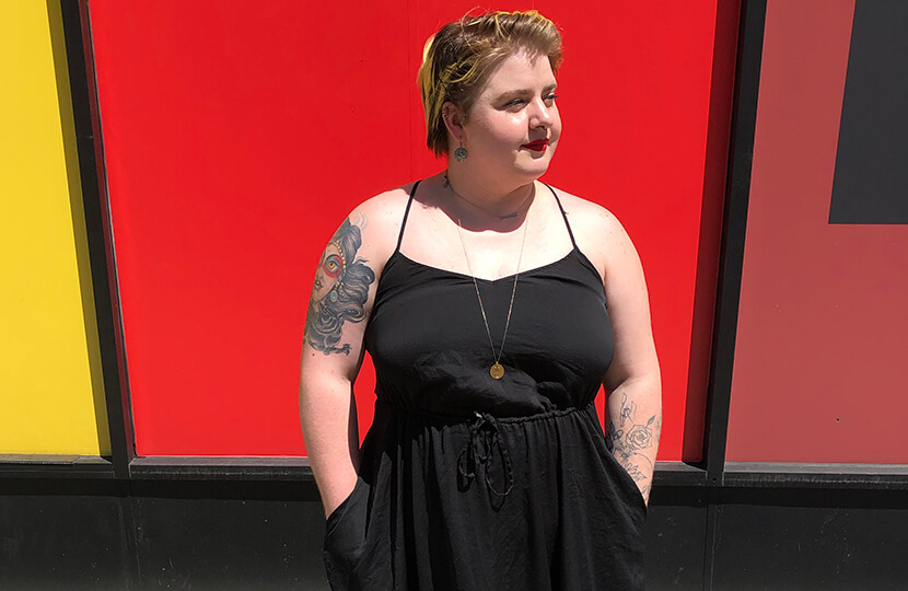 tattoos nikki bosso standing in front of red wall in black dress
