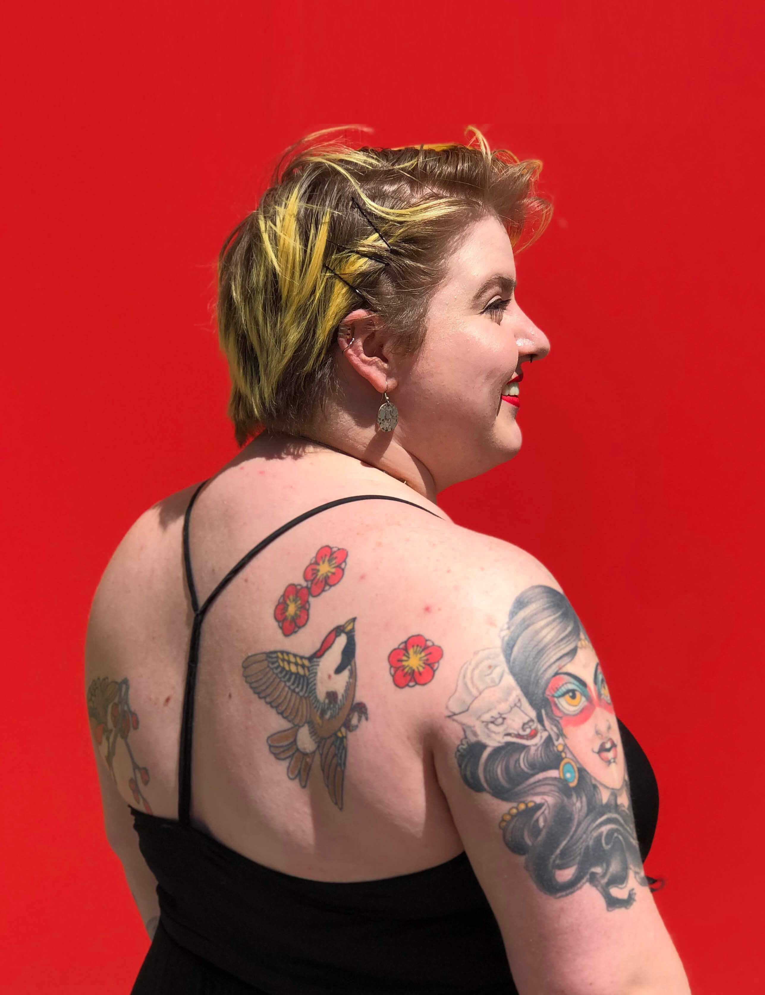 nikki bosso showing off tattoos on her back in front of red wall