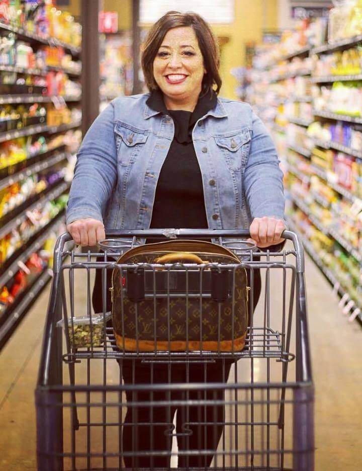 april wiencek the tipsy housewife pushing shopping cart in plus size denim jacket and black outfit