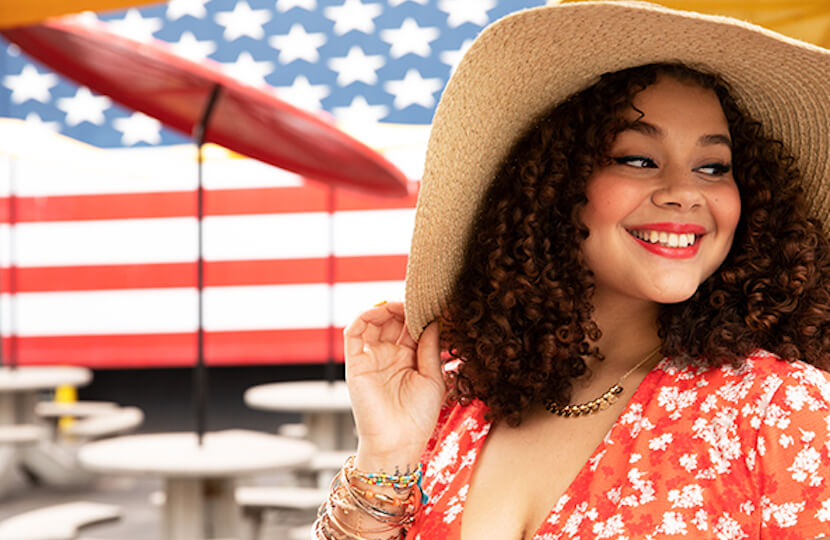 Model in red dress and straw hat, in front of an American flag.