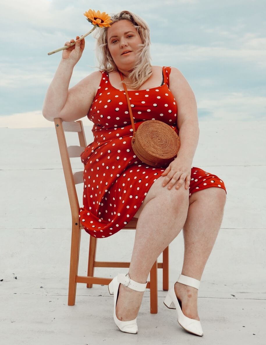 plus size woman sitting in chair in red polka dot dress with white shoes and bag
