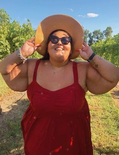 woman in plus size red dress and floppy hat